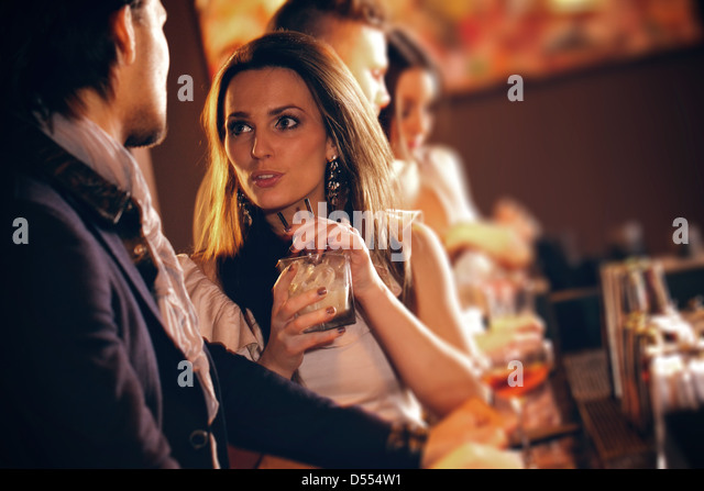 Young woman with a glass of wine talking to a man at the bar - Stock Image
