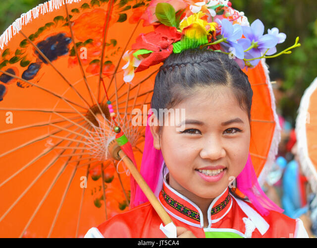 Smiling Thai Chinese Girl in Traditional Dress with Orange Parasol, Northern Thailand. - Stock Image