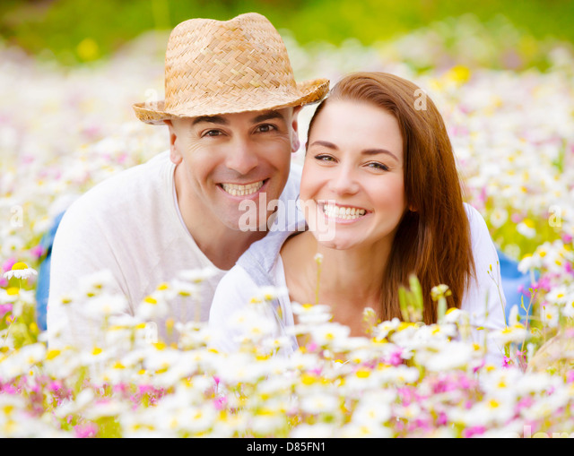 Portrait of cheerful young family laying down on floral field, having fun outdoors, summer holiday, romance and - Stock-Bilder
