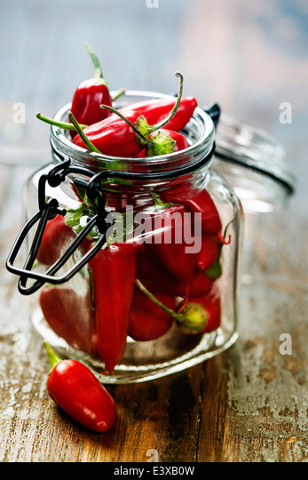 Red Hot Chili Peppers over wooden background - Stock Image