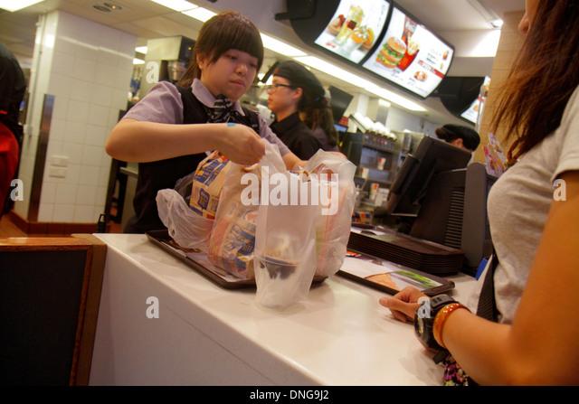 Hong Kong China Kowloon Sham Shui Po McDonald's fast food restaurant counter employee job Asian woman customer - Stock Image