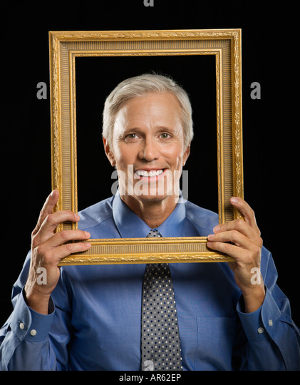 Caucasian middle aged businessman smiling through empty picture frame in front of face - Stock Image