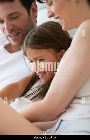 Parents and daughter reading together - Stock Image