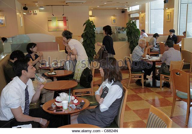 Tokyo Japan Ryogoku restaurant interior cafeteria business tables Asian boy girl student teen - Stock Image