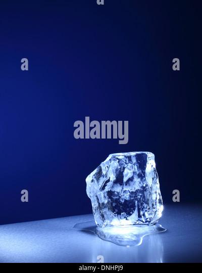 A large square cube / block of ice slowly melting. - Stock-Bilder