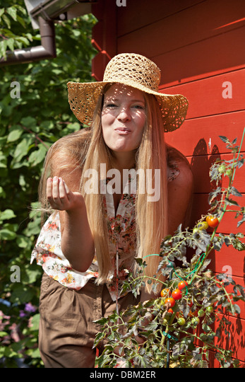 Mid adult woman eating tomatoes in vegetable garden, Munich, Bavaria, Germany - Stock-Bilder