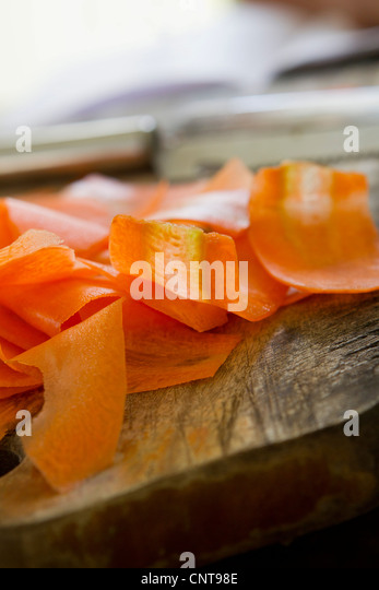 Thin slices of carrot on cutting board - Stock Image