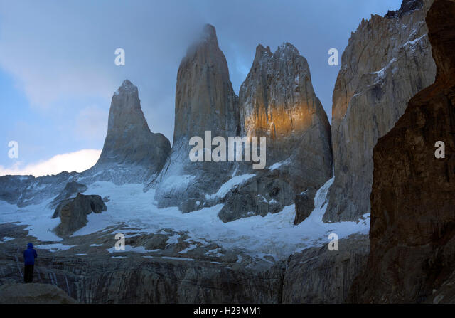 Trekker contemplating the sunrise over the Torres del Paine. Torres del Paine National Park. Patagonia. Chile - Stock Image