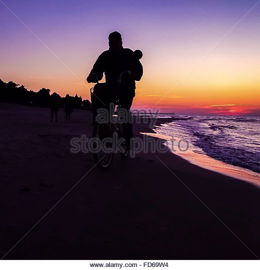 Silhouette Of A Man Cycling On The Beach - Stock Image