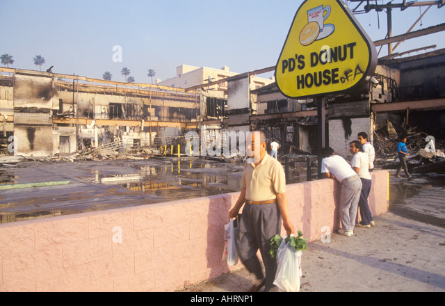 Man walking past donut shop destroyed during 1992 riots South Central Los Angeles California - Stock Image