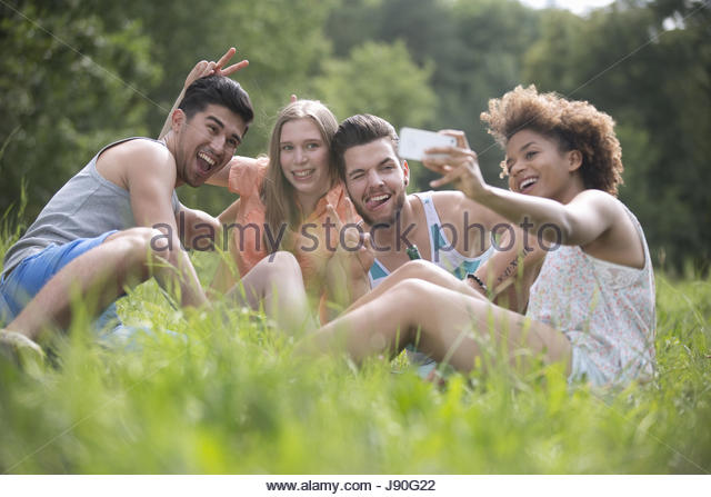 Young Couples Pose For Selfie Sitting On Grass - Stock-Bilder