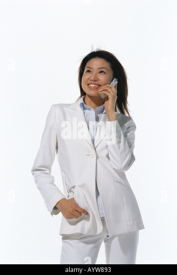 Woman in white suite talking on a cell phone - Stock-Bilder