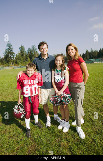 Football player and cheerleader with parents - Stock Image