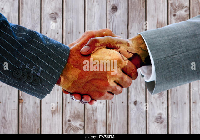 Composite image of business people shaking hands - Stock Image