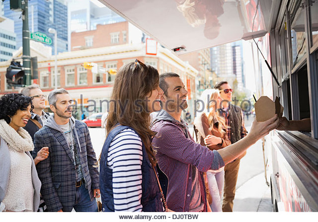Couple buying a meal from a food truck - Stock Image