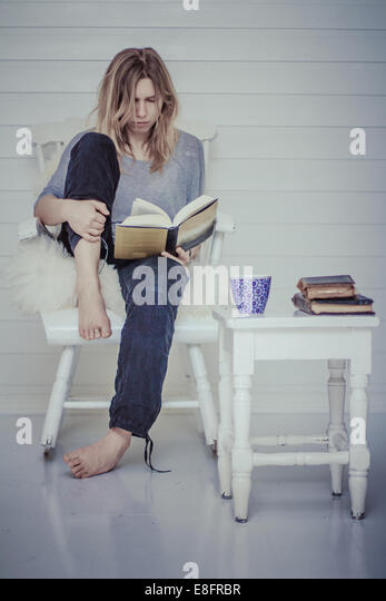 Portrait of a woman sitting on chair reading a book with cup of tea - Stock Image
