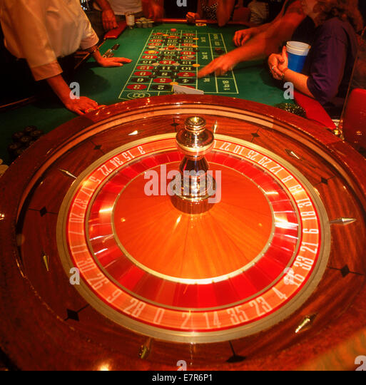 Gambling at the roulette table with chips and spinning wheel - Stock Image