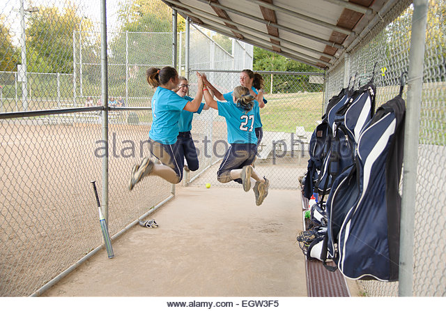 Soft ball team jumping up and giving high fives. - Stock Image