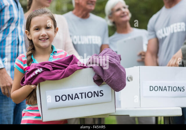 Happy volunteer family holding donation boxes - Stock Image