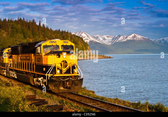 An Alaska Railroad passenger train rounds a corner along Turnagain Arm near Bird Creek, Southcentral Alaska, Summer - Stock Image