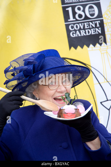 a queen Elizabeth II impressionist tucks into a Christmas pudding - Stock Image