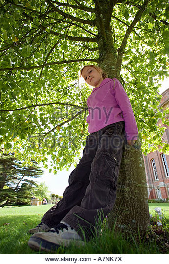 Girl 7 9 wearing purple top and combat trousers leaning against tree trunk in garden head cocked portrait low angle - Stock Image
