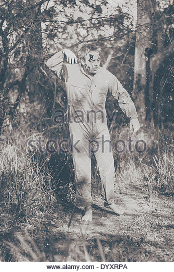 Vintage black and white horror photograph of a walking dead zombie wearing workers overalls starting a wave of terror - Stock Image