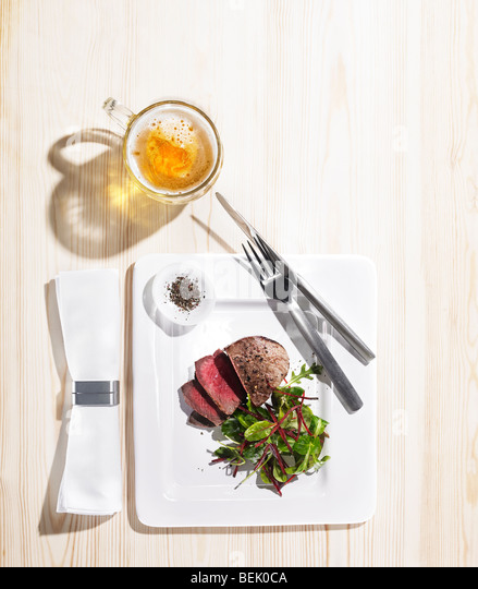 roast beef served with a salad of spinach and beetroot, black pepper and a pint of beer - Stock Image