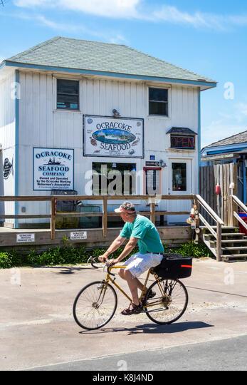 North Carolina NC Outer Banks Ocracoke Island Ocracoke Seafood Company fishmonger exterior man riding pedaling bicycle - Stock Image