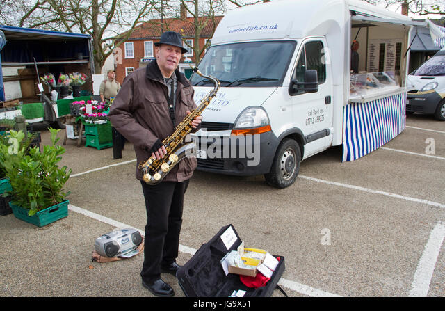 Middle-aged busker playing tenor sax on a Suffolk street market - Stock Image