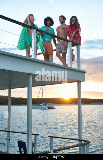 Young friends hanging out and drinking on summer houseboat at sunset - Stock-Bilder