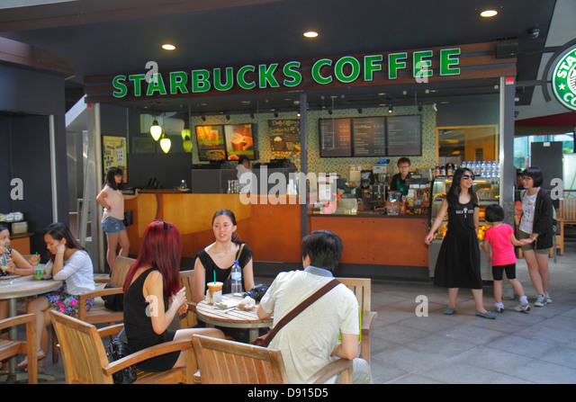 Singapore Singapore River Marina Bay Merlion Park Starbucks Coffee cafe Asian man woman tables - Stock Image