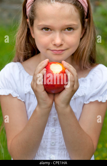 Girl standing outside in a field and shows a half-eaten apple - Stock Image