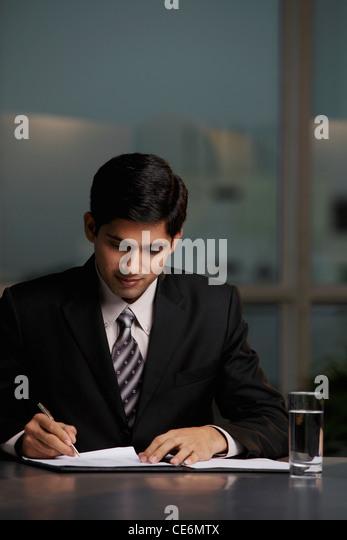 Indian man writing at table - Stock Image