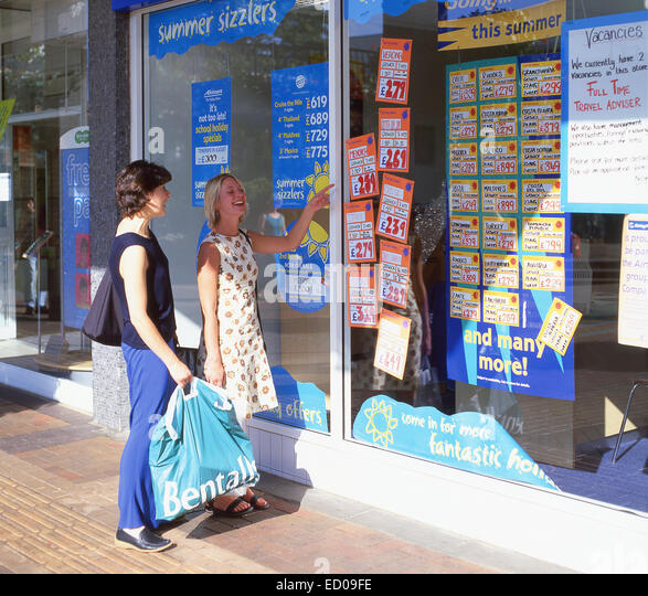 Young women looking at travel agents window, Bracknell, Berkshire, England, United Kingdom - Stock-Bilder