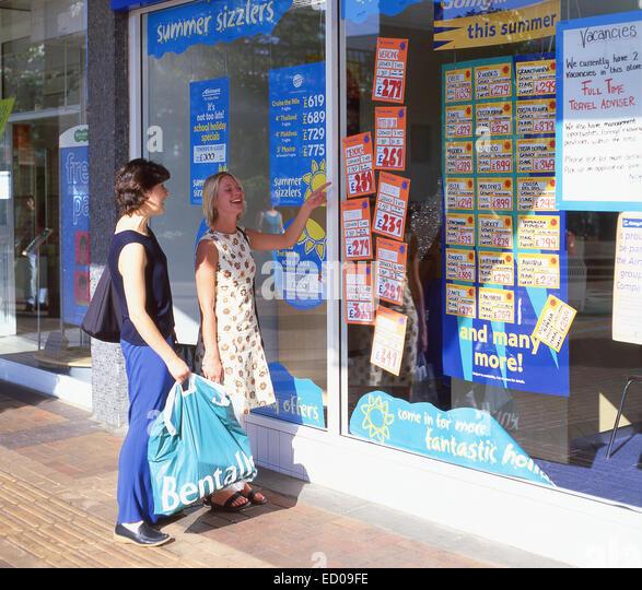 Young women looking at travel agents window, Bracknell, Berkshire, England, United Kingdom - Stock-Bilder