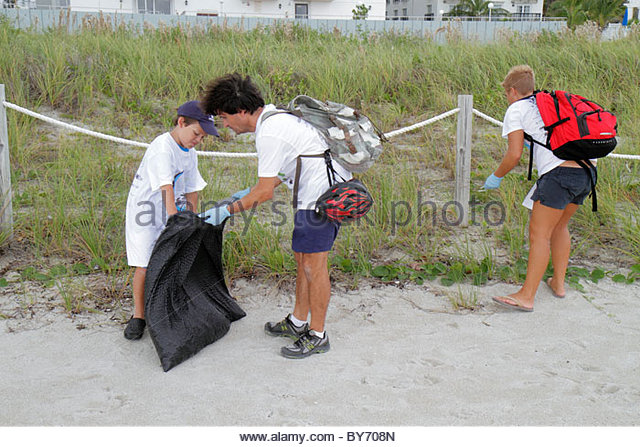 Miami Beach Florida Coastal Cleanup Day volunteer litter trash pollution public beach pick up family father son - Stock Image