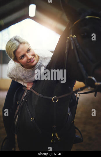 Smiling blonde female sitting astride black horse leaning on its' back. - Stock Image
