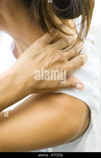 Woman touching the nape of her neck, side view, cropped - Stock Image