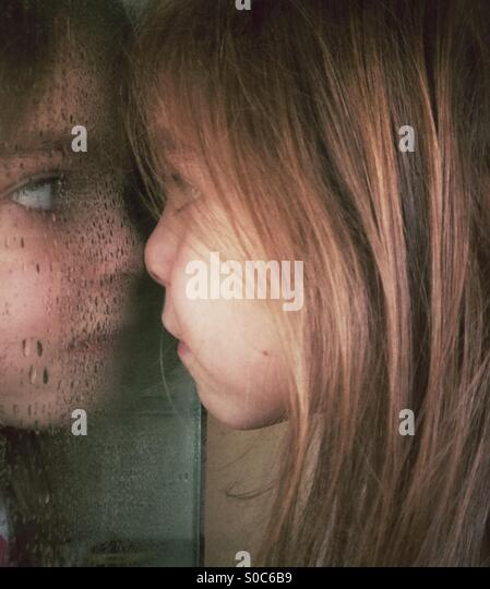 Girl pressing her nose against wet bathroom mirror - Stock Image