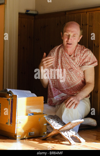 Hare Krishna devotee takes a class to learn about passages from the Bhagavad Gita - Stock Image