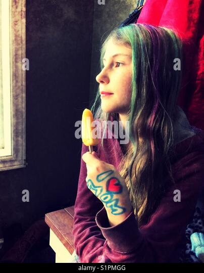 Preteen girl with dyed hair and 'I ❤️MOM' drawn on hand daydreaming by window while holding orange frozen - Stock Image