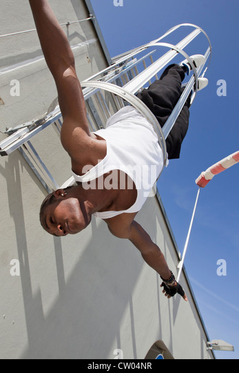 Man playing in safety escape of building - Stock Image