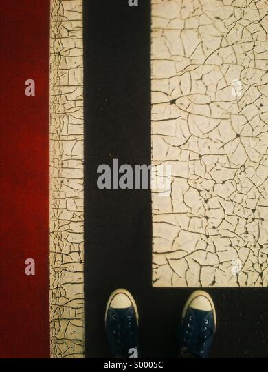 Looking down at feet on cracked painted surface - Stock Image