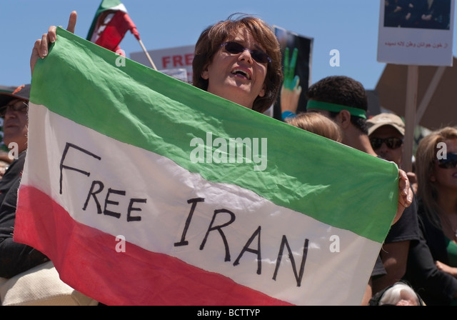 An Iranian woman holds an Iranian Flag with 'Free Iran' written across it during a demonstration in San - Stock Image
