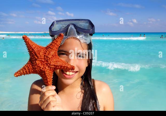 latin tourist girl holding starfish in tropical beach - Stock Image