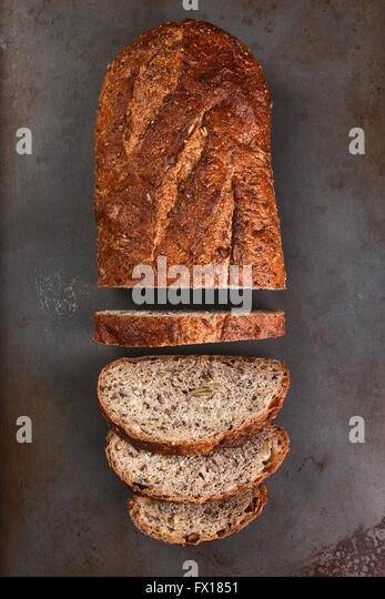 Top view of a loaf of multi-grain bread on a baking sheet. The loaf is partially sliced, - Stock Image