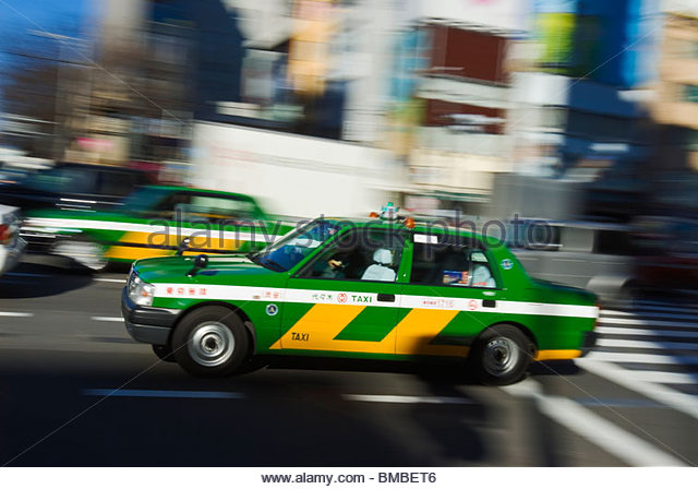 Colorful taxi speeding through traffic. - Stock Image