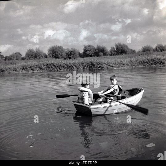 1950s historical picture, two young boys wearing life jackets rowing a small boat or dinghy down a quiet calm river - Stock Image