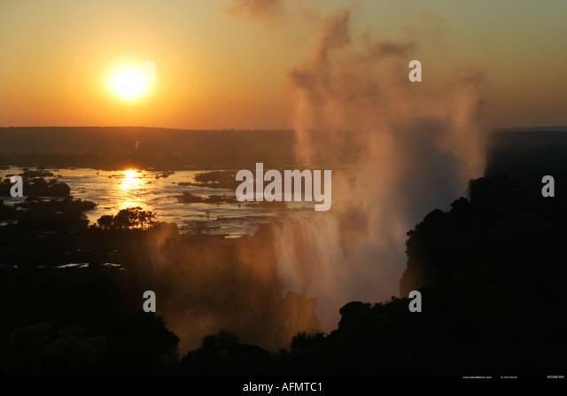 Sun rising over Victoria Falls Zimbabwe - Stock Image